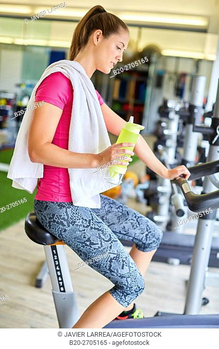 Woman training in gym, Elliptical bike
