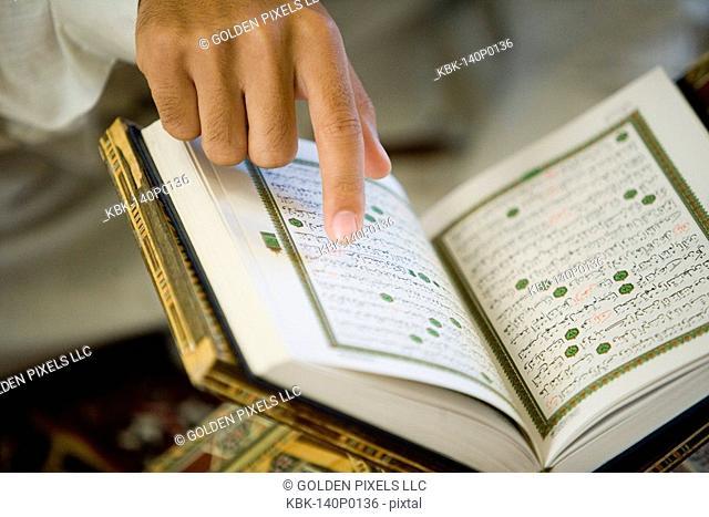 Close-up of a hand pointing at Koran