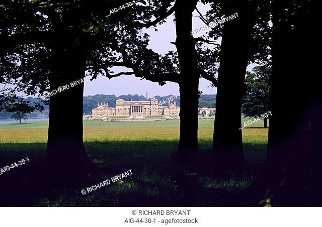 Holkham Hall, Norfolk. A historic 18th century Palladian mansion in parkland. Mature trees in the foreground
