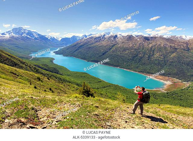 Male hiker taking a picture of Eklutna Lake and the Chugach Mountains from the Twin Peaks Trail, Chugach State Park, Southcentral Alaska, Spring, HDR