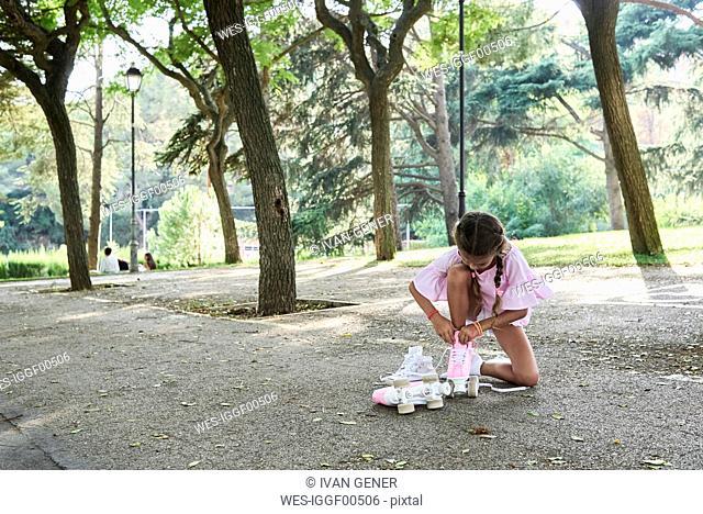 Little girl tying pink roller skates in a park