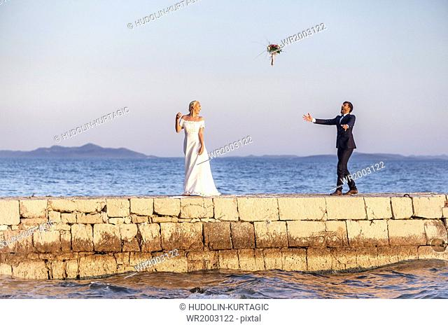 Bride and groom on pier throwing bouquet into air