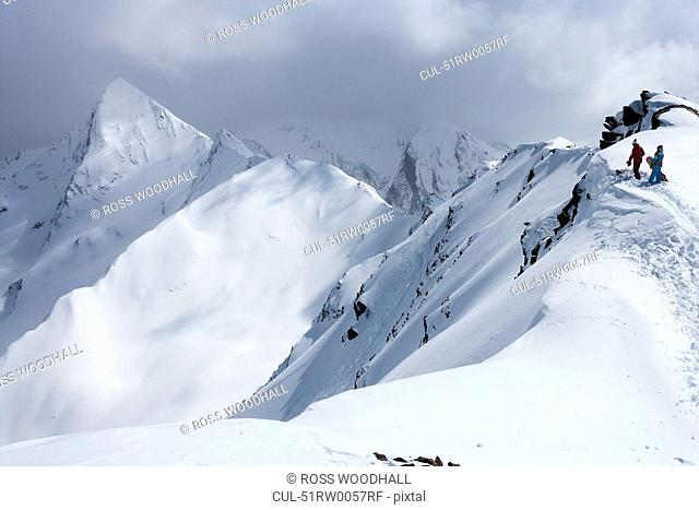 Snowboarders climbing snowy slope