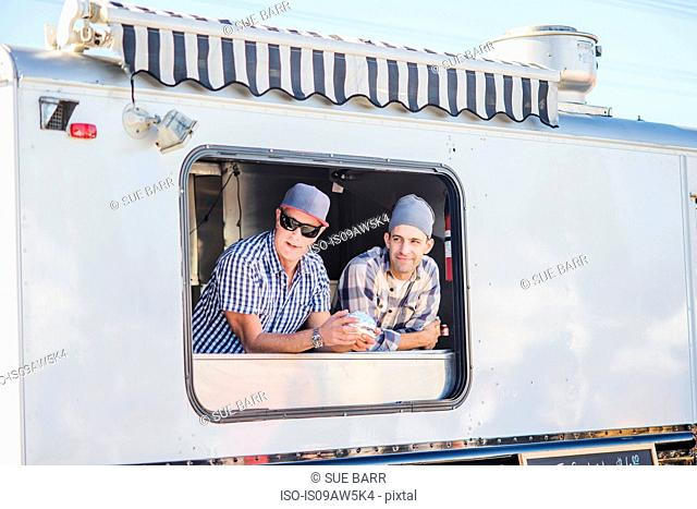 Men wearing chefs hats looking out of catering van hatch