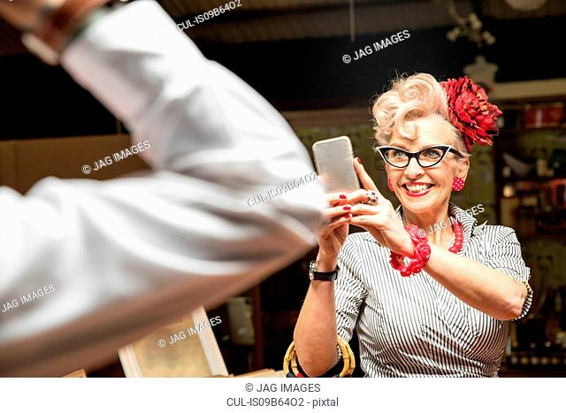 Quirky vintage woman photographing boyfriend in antiques emporium