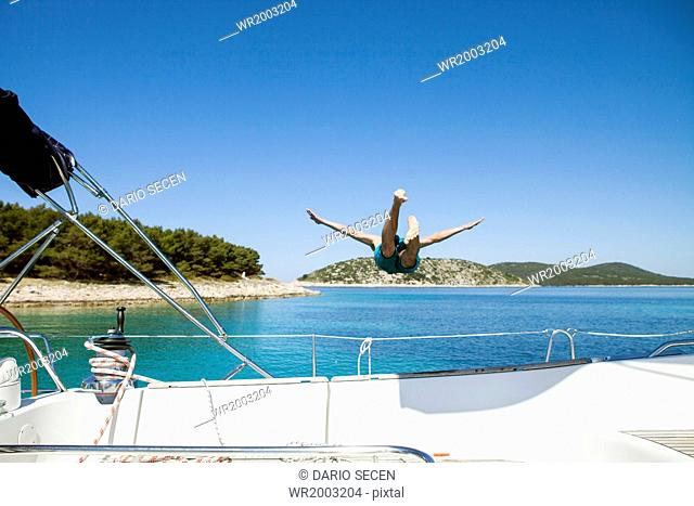 Young man diving into water from sailboat, Adriatic Sea