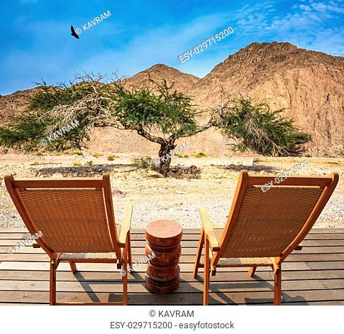 Two convenient chaise lounges and small table stand for tourists. Walking route on picturesque Black canyon