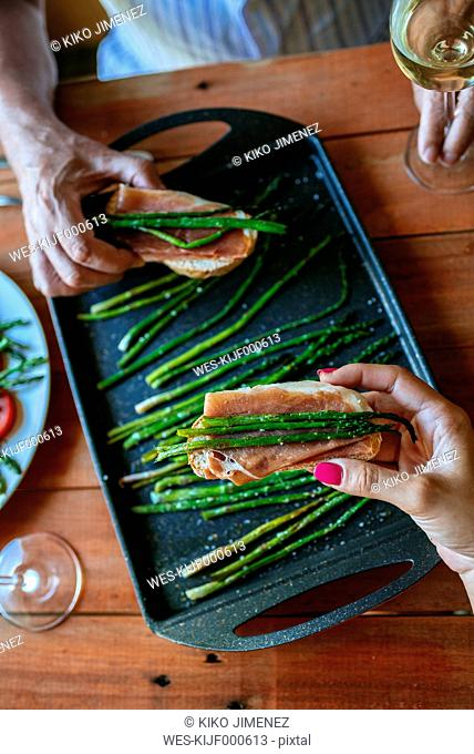 Hands taking bread slices with cured ham and grilled green asparagus