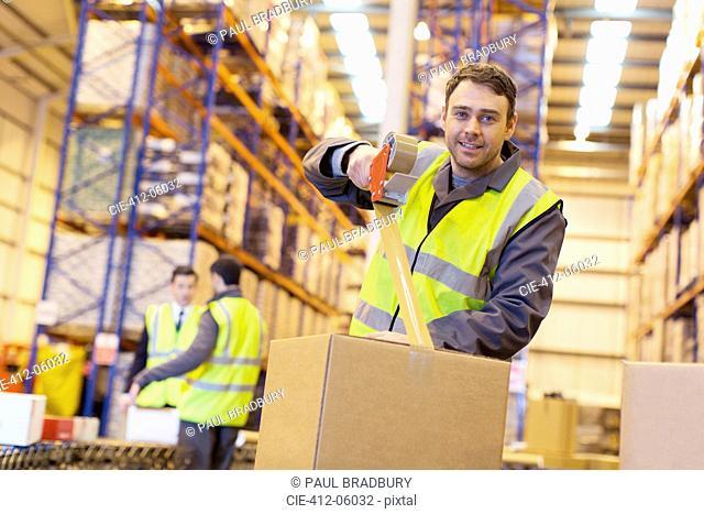 Worker taping cardboard box in warehouse