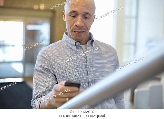 Mature businessman using smartphone in office