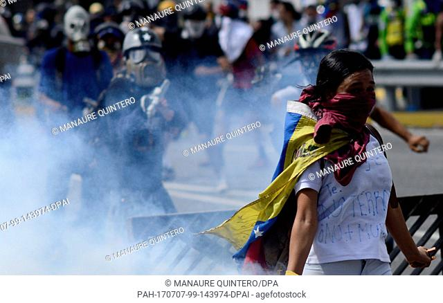 An anti-government demonstrator throws back a tear gas grenade to security forces in Caracas, Venezuela, 6 July 2017. Demonstrators had tried to enter the...