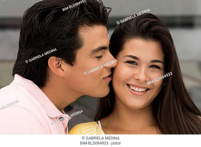 Hispanic man kissing girlfriend