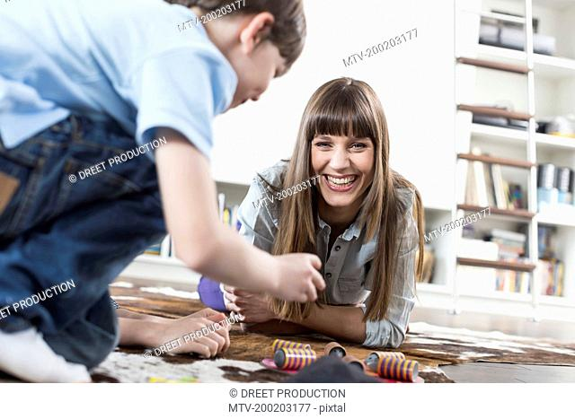 Mother and son playing board game, smiling