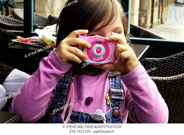 A little girl plays at being a photographer
