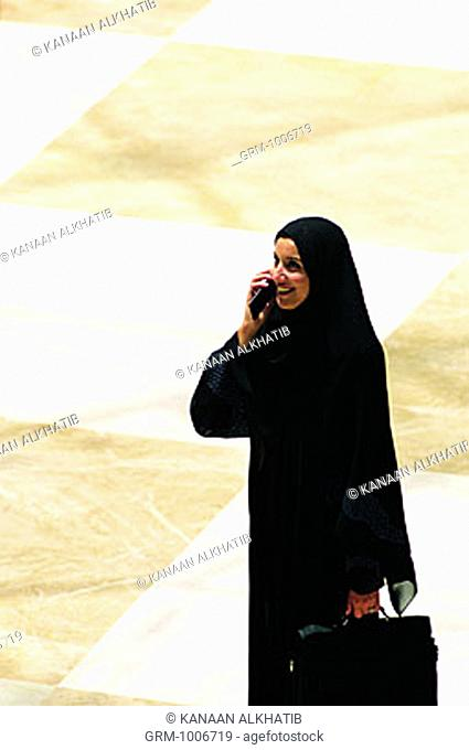 Emirati businesswoman using mobile phone