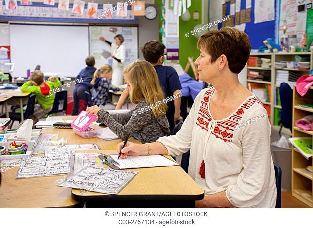 A professional observer takes notes while sitting in an elementary school classroom in Mission Viejo, CA. Note that the students and teacher ignore the observer...