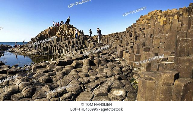 Northern Ireland, County Antrim, Giants Causeway, Tourists exploring the interlocking basalt columns of the Giants Causeway