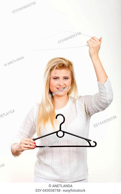 Wardrobe accessories concept. Blonde happy woman holding clothes hanger. Studio shot on light background