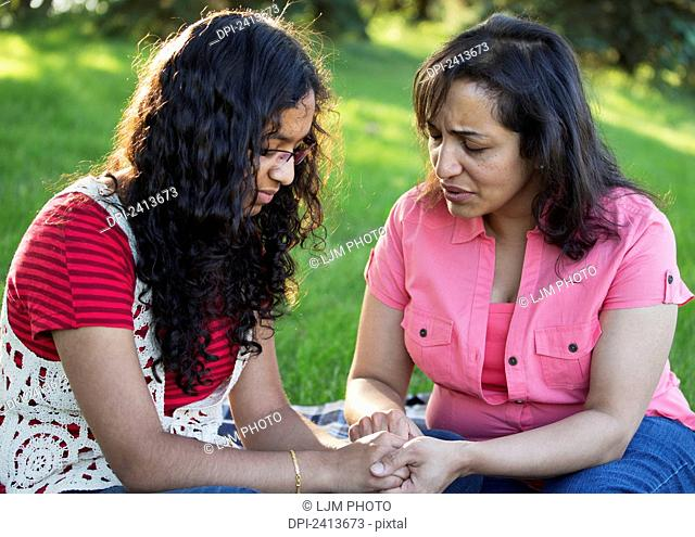 Mother and daughter praying together in a park; Edmonton, Alberta, Canada