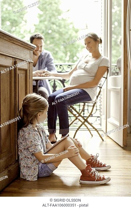 Girl sitting on floor with digital tablet as parents chat in background