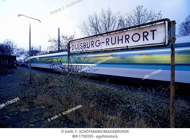 Overgrown platform, train passing, Duisburg-Ruhrort suburban train station, North Rhine-Westphalia, Germany, Europe