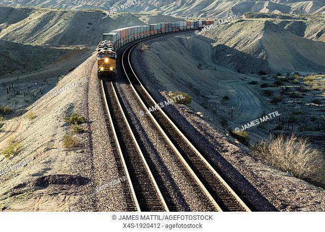 A frieght train rounds a bend in the aride California desert in late afternoon