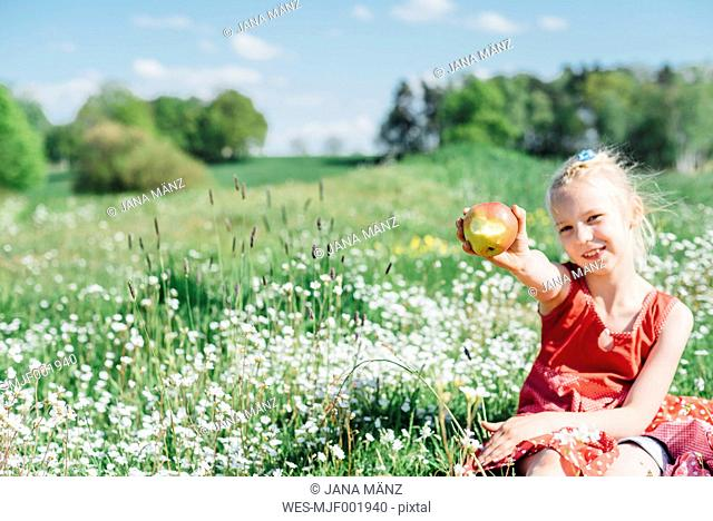 Smiling girl sitting in meadow holding an apple