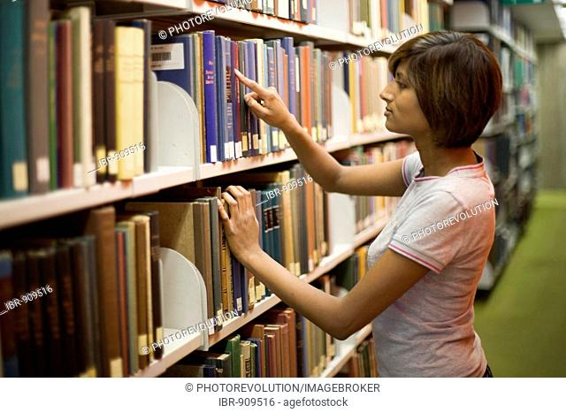 Young dark-haired female student searching for a book on a bookshelf in a library