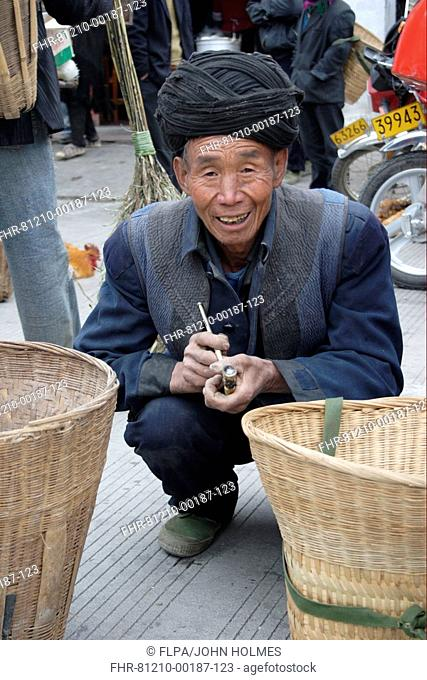 3bfab3ee0 'Black Yi' ethnic minority, elderly man smoking pipe at market, Sichuan,