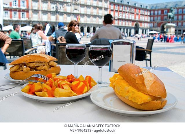 Fried squids sandwich, patatas bravas and Spanish omelet sandwich with two glasses of red wine in a terrace. Main Square, Madrid, Spain