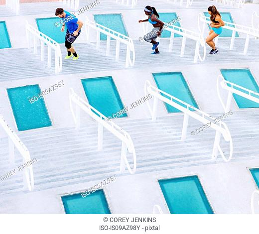 Man and two women training, stepping sideways on stairway at sport facility, downtown San Diego, California, USA