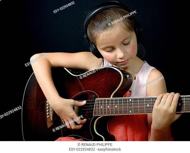 a pretty little girl playing guitar