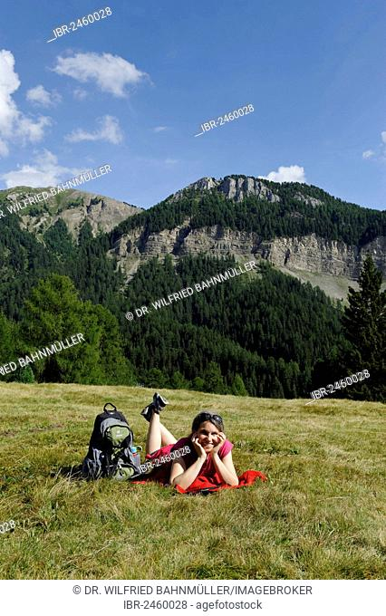 Hiker lying on the Raschoetz alp, Col de Raiser mountain at the back, near St. Ulrich, Val Gardena valley, Province of Bolzano-Bozen, Alto Adige, Italy, Europe