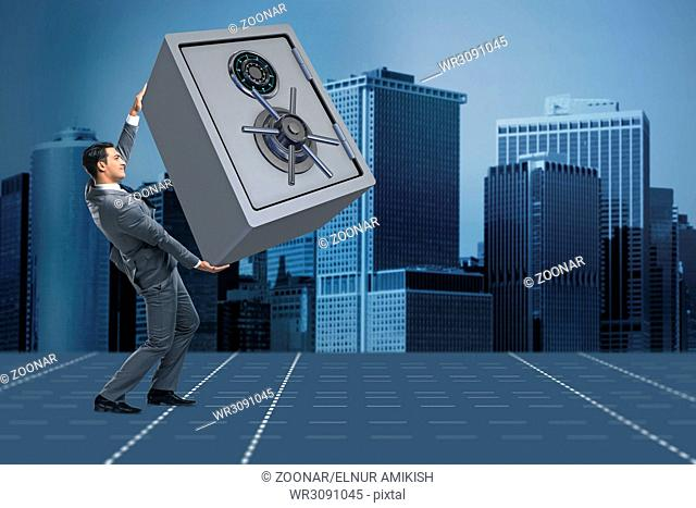 Businessman carrying metal safe in security concept