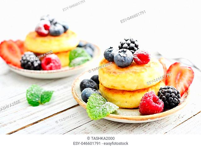 Cottage cheese pancakes, syrniki, curd fritters with fresh berries on wooden background