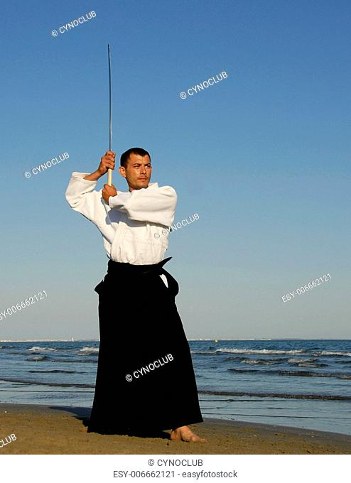 a young man are training in Aikido on the beach