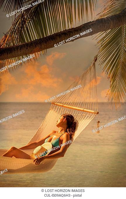 Mid adult woman relaxing in hammock, Ari Atoll, Maldives