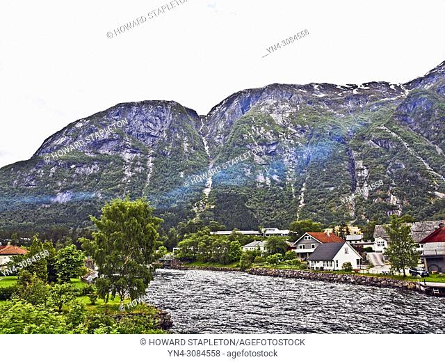 The Eio river runs through the village of Eidfjord, Norway. Mountains surround the town. The Eio river is only 1. 3 miles long and runs from Lake Eidfjord into...