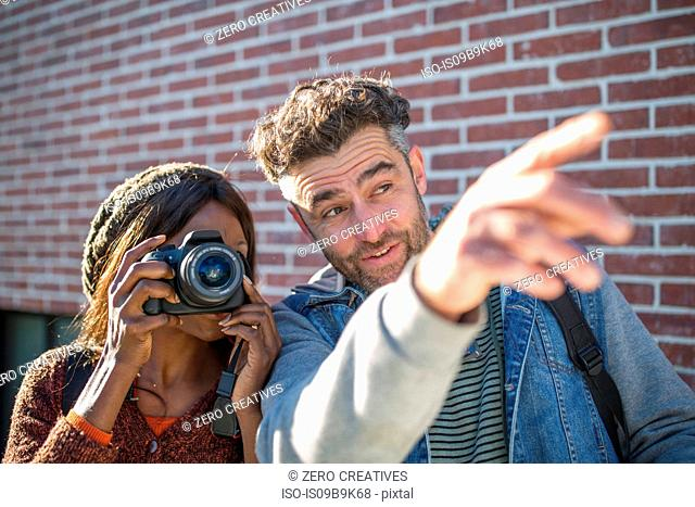 Man and woman outdoors, man pointing ahead, woman looking through camera