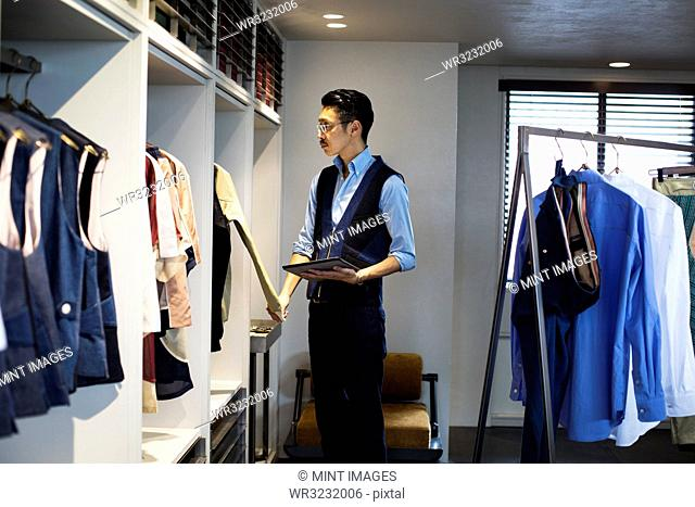 Japanese salesman with moustache wearing glasses standing in clothing store, looking at clothes on a rail, holding digital tablet