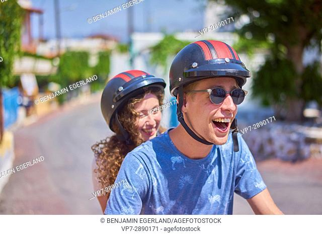 exhilarated young couple enjoying road trip with moped. Hersonissos, Crete, Greece