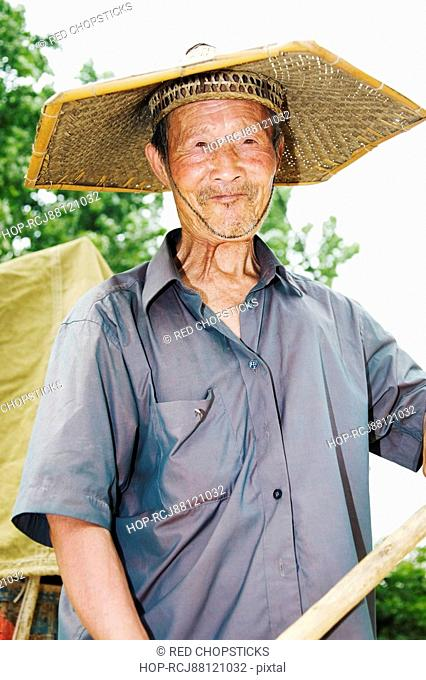 Close-up of a farmer wearing an Asian style conical hat, Zhigou, Shandong Province, China