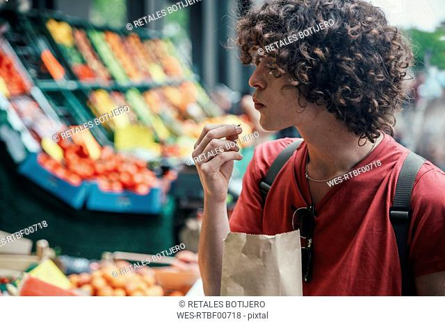 Young man eating cherries in front of street fruit stand