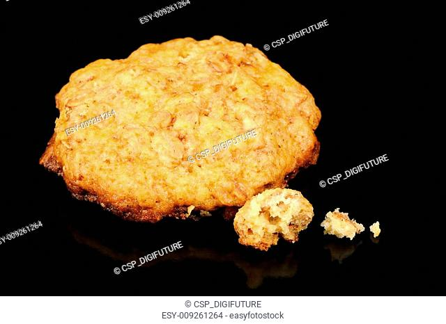 Oatmeal Cookie with Crumbs on Black Background