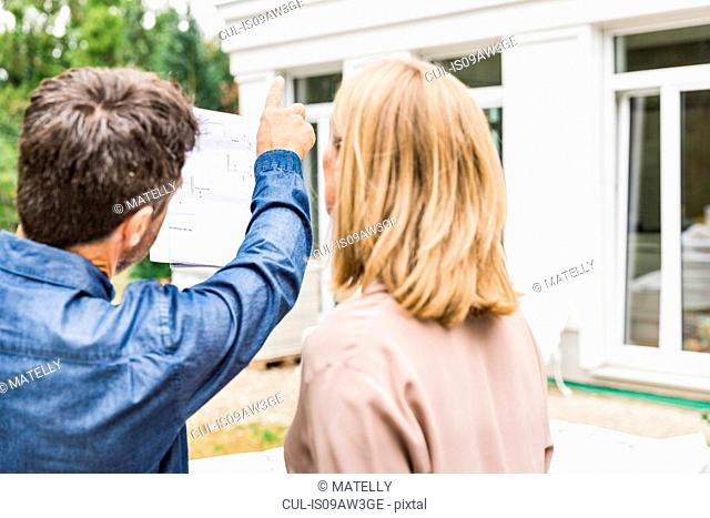 Rear view of architect discussing blueprints for house exterior with homeowner pointing