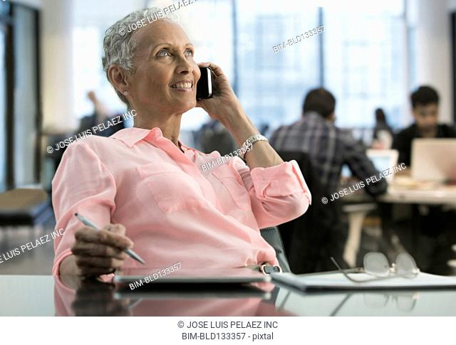 African American businesswoman on cell phone in office