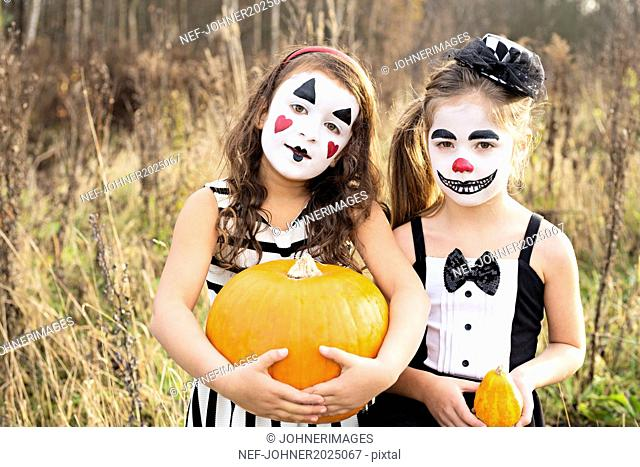 Girls with painted faces holding pumpkins