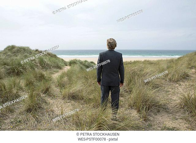 UK, Cornwall, Hayle, businessman standing in beach dunes looking at view