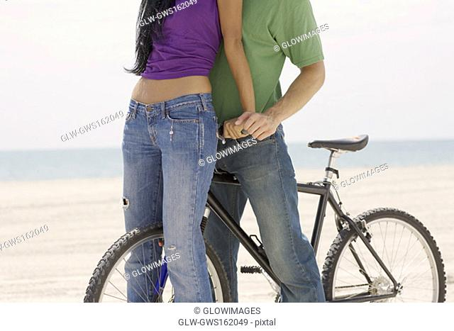 Close-up of a young couple standing on the beach with a bicycle