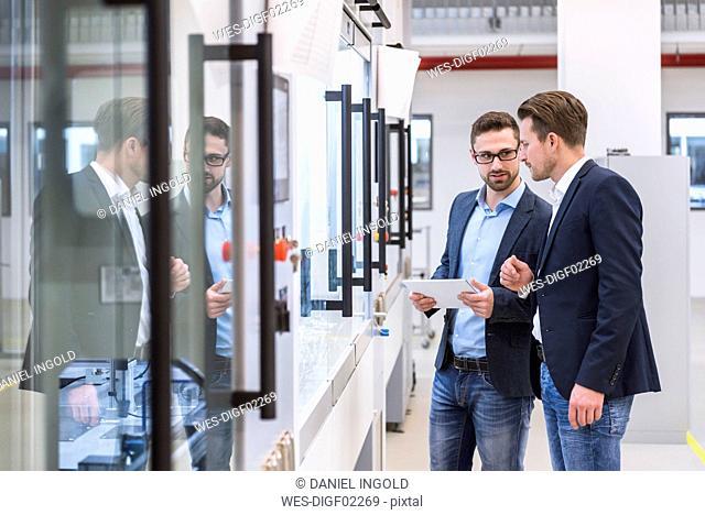 Two men with tablet in factory shop floor